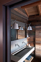 A wash basin in reconstituted stone contrasts with the larchwood cladding on the walls of this contemporary bathroom