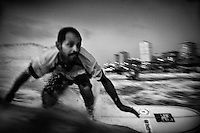 38 year old surfer Mohammed Abu Jayab rides a wave in the Mediterranean Sea off Gaza City. Abu Jayab is the leader of a surf group in Gaza and one of the pioneers of the sport in the coastal enclave.