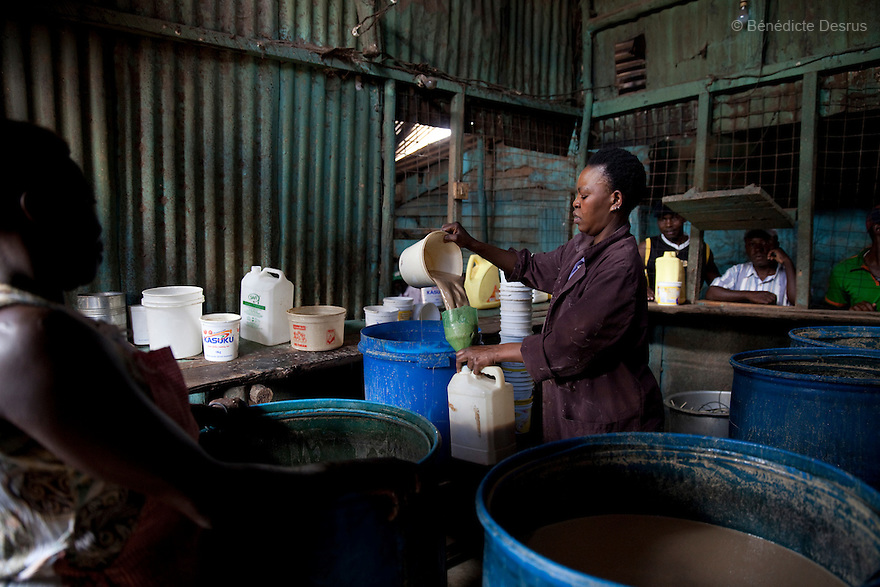 Alice(R) and Mary(L) working at the Madiaba Busaa Club in a Nairobi slum on april 7, 2013. Both have been selling Busaa, a traditional fermented beer, for many years. Busaa is made by crudely fermenting maize, millet, sorghum or molasses. At Kshs 35 per liter it is much cheaper than a Kshs120 half-liter bottle of commercial beer. The local brew was legalised in 2010 and since then busaa clubs have become increasingly popular. Drinking is on the rise in Kenya, especially among young people. Photo by Benedicte Desrus