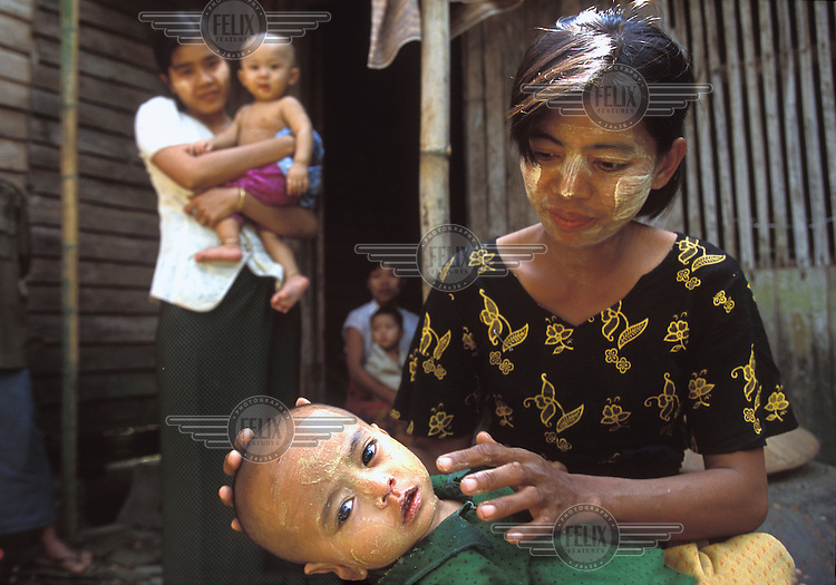 "Traditional ""tanaka"" is applied to a baby's face in Khat-Tu village. Tanaka is believed to be good for the skin and keep away germs and evil spirits. All Burmese women and children wear tanaka, which is made by grinding the bark of sandalwood."