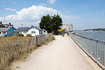 Sea wall pathway houses and martello tower at Felixstowe Ferry, Suffolk, England, UK