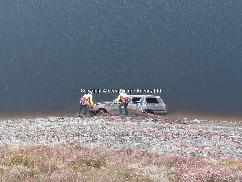 """Pictured: Brecon Mountain Rescue personnel scale down Llyn Brianne to examine an old Ford Sierra car discobered in mid Wales, UK.<br /> Re: Rescuers had to climb down the side of a reservoir to check if anyone was inside the old shell of a Ford Sierra car that was exposed after water levels dropped.<br /> Brecon Mountain Rescue Team were called by Dyfed Powys Police to investigate the strange discovery at Llyn Brianne Reservoir.<br /> Volunteers used ropes to get to and inspect the car.<br /> The service tweeted: """"The vehicle had been there for many years & (more importantly) was unoccupied""""."""