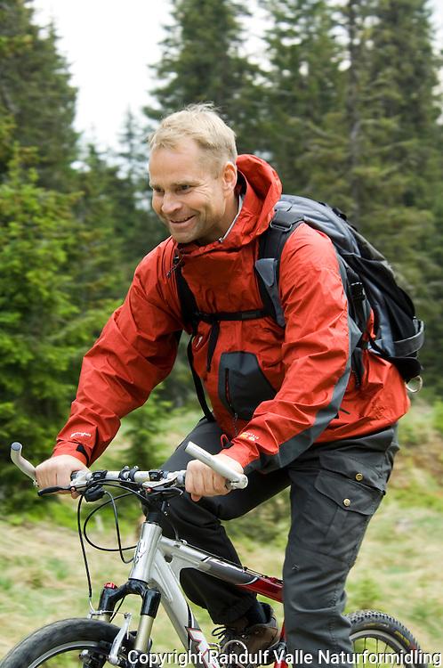 Mann sykler på grusvei i granskog ---- Man riding a bike on a road in forest