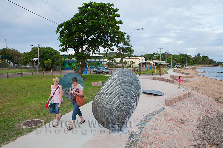 Tourists walk past public artworks on the Victoria Parade foreshore.   Thursday Island, Torres Strait Islands, Queensland, Australia