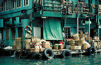 Dock in Hong Kong Harbor is stacked with supplies, goods. Hong Kong, China.