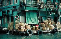 Dock in Hong Kong Harbor is stacked with supplies, goods. Hong Kong, China.