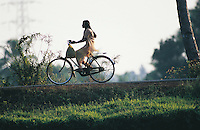 A woman, looking elegant in her salmon-pink shalwar-kameez, cycles along the river bank in the Backwaters of Kerala, South India. In this flat area of southern India, the bicycle is a pleasant alternative to the infrequent, dangerous, hot and overcrowded buses.
