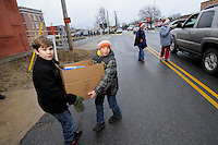 NWA Media/ J.T. Wampler - Andrew Williams, left, of  Bella Vista and Dylan Bertrand of Bentonville carry a box of food to people lined up in cars Wednesday Dec. 24, 2014 in Bentonville. The Bentonville Kiwanis  Club distributed 540 boxes of food to area families Wednesday.
