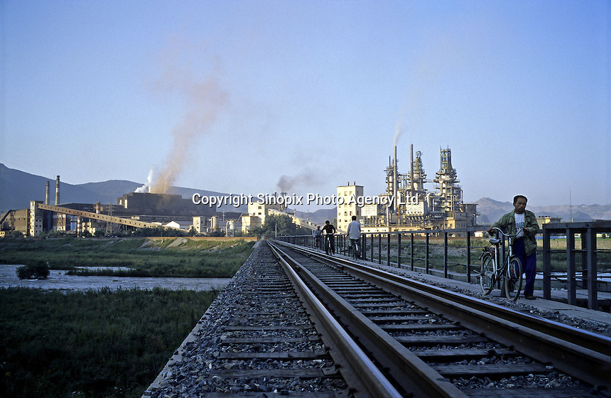 A cyclist passes the railway in front of the smog from Beitai Iron & Steel Group (Beigang Group), China's 5th-largest steelmaker in Benxi, Liaoning province..22 Aug 2005