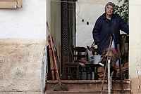 Pictured: An elderly woman stands on her porch with a few of her belongings.<br /> Re: People have died, some still missing and severe damage caused by heavy rain and flash flooding in the area of Mandra, near Athens, Greece. Thursday 16 November 2017