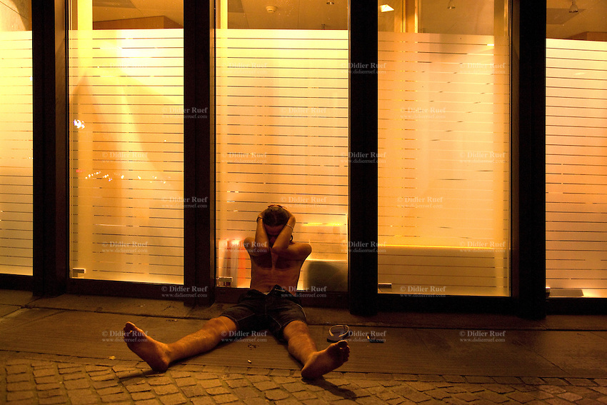 Switzerland. Geneva. A man is seated on the ground because he cannot breathe anymore after receiving pepper spray in his face. The inmate is an arab man from the Maghreb area and will be arrested by the police for stealing goods in a car. Illuminated bank window in the financial district. 30.06.12 © 2012 Didier Ruef