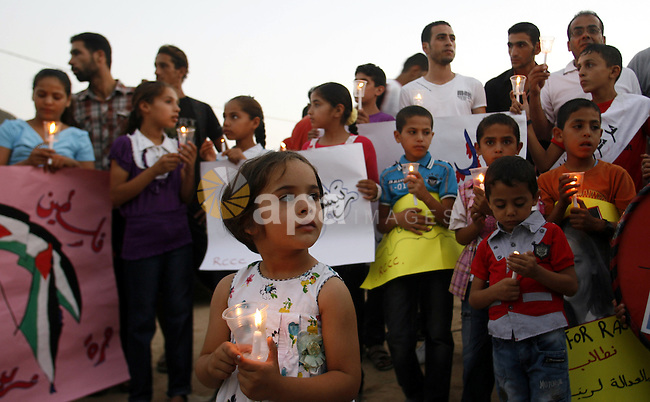 Palestinian children hold candles during a protest in Rafah in the southern Gaza Strip, against an Israeli court's ruling, August 29, 2012. The Israeli court on Tuesday cleared Israel's military of any blame for the death of American activist Rachel Corrie, who was crushed by an army bulldozer during a pro-Palestinian demonstration in Gaza. Photo by Eyad Al Baba