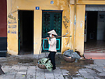 Hanoi, Vietnam, A woman carrying two baskets walk past a historic city building that is marked by demolition company graffiti. photo taken July 2008.