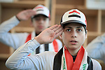 Boys salute as they lead participants in singing the national anthem during a November 30, 2018, book festival in Mosul, Iraq. The event celebrated the restoration of cultural freedom since the defeat of the Islamic State group, also known as ISIS.