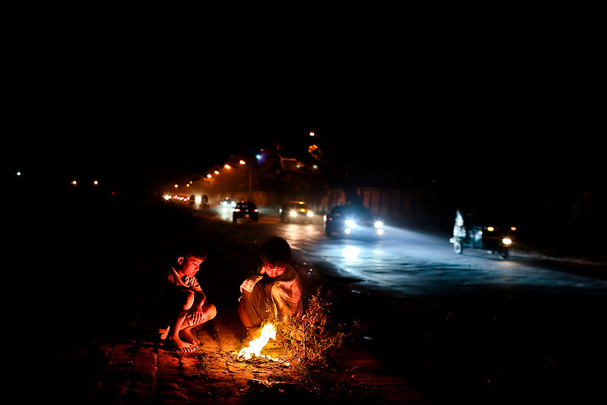 Bangladeshi street children warm themselves near a bonfire by the side of a road, as vehicles drive past in Dhaka, Bangladesh.