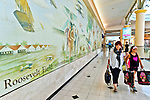 Garden City, New York, USA. 15th August 2013. At Roosevelt Field Shopping Mall, a mother and daughter carrying shopping bags walks past a wall mural depicting aviation scenes from the site's past. Roosevelt Field is on the site where world famous aviator Charles Lindbergh took off for his historic solo flight across the Altantic Ocean to France in 1927. The mall is one of the 10 largest in the United States of America.