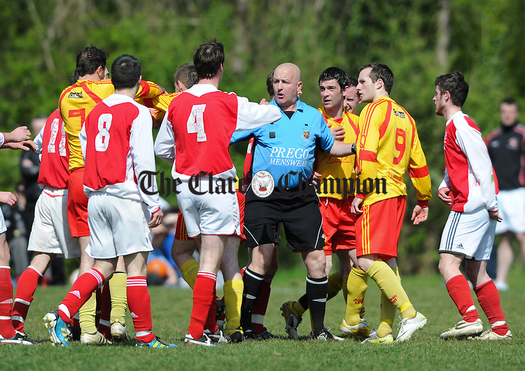 Referee Martin O Brien gets between Newmarket and Avenue United players during their game at Lees road. Photograph by John Kelly.