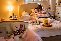 A woman breastfeeding 5 month old twins at the same time on her bed in her bedroom.<br /> <br /> Image from the &quot;We Do It In Public&quot; documentary photography project collection: <br />  www.breastfeedinginpublic.co.uk<br /> <br /> Hampshire, England, UK<br /> 11/02/2013