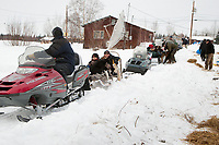 Volunteers at Nikolai take 28 dropped dogs in a *wagon train* of snowmachines from the checkpoint to the airstrip to be flown out on a Pennair Caravan back to Anchorage during Iditarod 2009