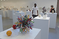 Surface to Structure origami exhibition at Cooper Union, New York. Gallery view. Event Horizon (left) designed and folded by Byriah Loper 2013. Little Roses Kusudama designed and folded by Maria Sinayskaya 2011 (red back). Star Icosahedron designed and folded by Evan Zodl 2012 (yellow front).
