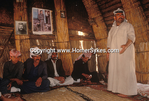 Marsh Arabs. Southern Iraq. Circa 1985. Marsh Arab men in traditional reed guest house called Mudhif. Photograph of Saddam Hussein on wall. Haur al Mamar or Haur al-Hamar marsh collectively known now as Hammar marshes Irag 1984