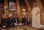Marsh Arabs. Southern Iraq.  Marsh Arab men in traditional reed guest house called Mudhif. Photograph of Saddam Hussein on wall. Haur al Mamar or Haur al-Hamar marsh collectively known now as Hammar marshes Iraq 1984