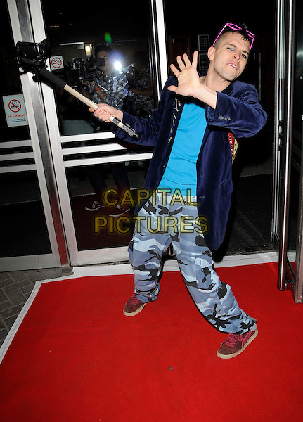 PETE BENNETT .Attends the Big Brother Celebriparty, .Indigo Club, O2 Arena, London, England, UK, September 6th 2009..full length blue velvet jacket trousers camouflage print grey gray pink sunglasses on head hand funny holding video camera on pole stick eyeshadow make-up filming .CAP/CAN.©Can Nguyen/Capital Pictures