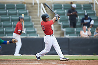 Camilo Quinteiro (12) of the Kannapolis Intimidators follows through on his swing against the Lexington Legends at Kannapolis Intimidators Stadium on August 4, 2019 in Kannapolis, North Carolina. The Legends defeated the Intimidators 5-1. (Brian Westerholt/Four Seam Images)