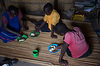 Uganda - Palorinya Refugee Camp - Three South Sudanese orphans having lunch in their house at the orphanage. <br /> Several unaccompanied minors fleeing South Sudan experience high level of trauma. Some have seen their parents or relatives killed by armed groups, others have been recruited and trained as child soldiers. Due to lack of resources, there is a high shortage of child protection officers to counsel them.