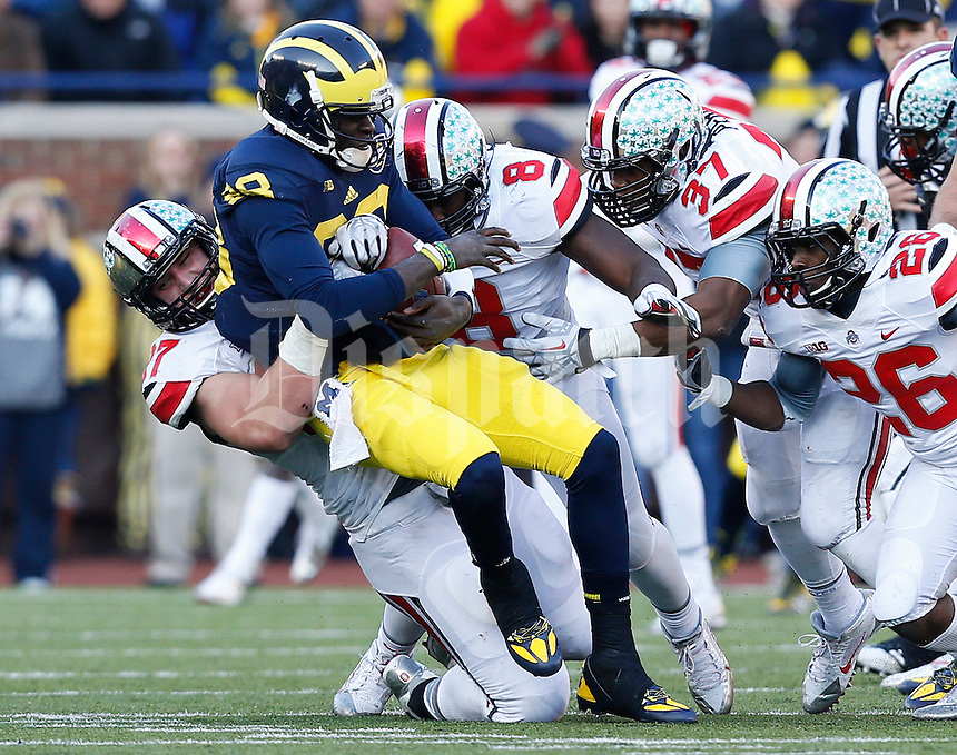 Ohio State Buckeyes defensive lineman Joey Bosa (97) sacks Michigan Wolverines quarterback Devin Gardner (98) in the fourth quarter of the college football game between the Ohio State Buckeyes and the Michigan Wolverines at Michigan Stadium in Ann Arbor, Michigan Saturday afternoon, November 30, 2013. The Ohio State Buckeyes defeated the Michigan Wolverines 42 - 41. (The Columbus Dispatch / Eamon Queeney)