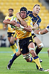 Hurricanes' loose forward Adam Hill, left, is tackled around the neck by ACT Brumbies' fullback Jesse Mogg, right, in the Super Rugby match at Westpac Stadium, Wellington, New Zealand, Friday, March 07, 2014. Credit: Dean Pemberton