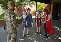 NWA Democrat-Gazette/BEN GOFF @NWABENGOFF<br /> Myra Cooper, 7, talks to her mom Kelsey Kennedy as stepmother Melissa Cooper, sister Elizabeth Cooper, 2, and father father Staff Sgt. William Cooper, all of Bentonville, look on Monday, May 8, 2017, after Staff Sgt. Copper surprised Myra in her classroom at Apple Glen Elementary School in Bentonville. Each week a parent comes in as a 'Mystery Reader' for their child's classroom at the school, with students receiving clues as to who it will be throughout the week. This week Myra was surprised by her father, who has been away from his family for over a year on deployment to Kuwait with the U.S. Army 77th Combat Aviation Brigade. Staff Sgt. Cooper read to the class from 'Harold and the Purple Crayon' by Crockett Johnson before taking Myra and the rest of their family to spend the day a the nearby Scott Family Amazeum.