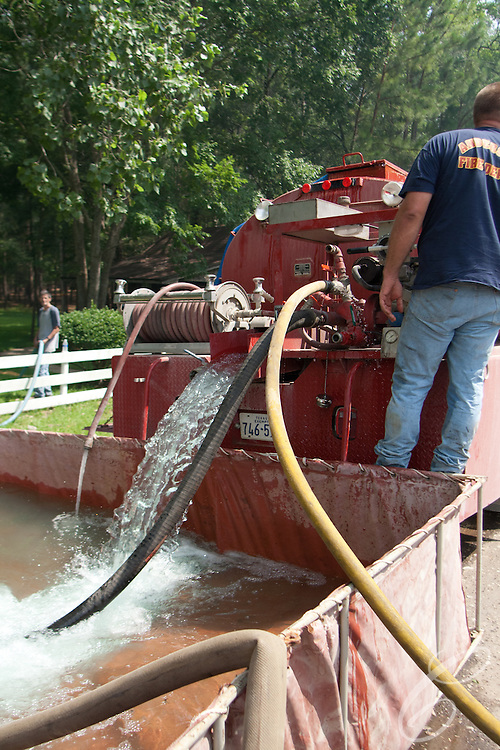 An Anderson fire truck pumps water from Ed and Dee Laitkep's pond into a temporary holding tank to fill trucks fighting the Dyer Mill fire in Grimes County for a third day on June 21, 2001.