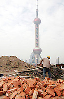 A construction worker on duty at a building site near the Oriental Pearl TV Tower in Shanghai, China. The Shanghai government announced recently that it will no longer consider real estate as one of the city's key sectors due to Beijing macro-economic control policies for the 11th five-year plan, instead the city will focus development in aviation and marine-related industries..