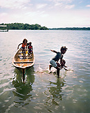 PANAMA, Bocas del Toro, young kids jump out of a dugout canoe into Almirante Bay, Central America