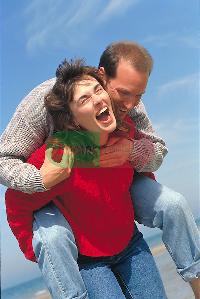 laughing woman carrying man at beach