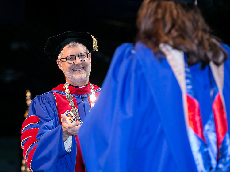 The Rev. Dennis H. Holtschneider, C.M., president of DePaul University, hands out diplomas to the graduates as the Driehaus College of Business held its commencement ceremony Sunday, June 12, 2016, at the Allstate Arena in Rosemont, IL. Nearly 1,400 students received their degrees. (DePaul University/Jamie Moncrief)Paul University/Jamie Moncrief)