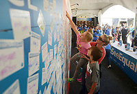 NWA Democrat-Gazette/BEN GOFF @NWABENGOFF<br /> Carrie Schweer of Bentonville lifts her daughter Ellie Schweer, 8, as son Matthew Schweer, 12, looks on Thursday, May 4, 2017, while adding their stickers to the 'We See Equal' wall in the Procter & Gamble booth in the Sponsor Village at Compton Gardens during the Bentonville Film Festival. The family were visiting the festival to celebrate Matthews birthday.