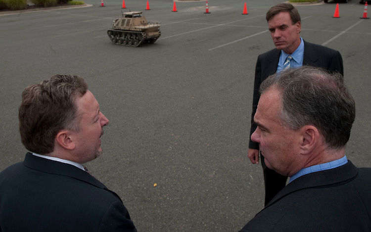 """UNITED STATES - SEPT 17 : Dr. Tom Van Doren the COO of HDT Robotics conducts a tour in Fredericksburg Virginia on September 17, 2012. Here Sen. Mark Warner, D-VA., and Gov. Tim Kaine, D-Va., watch a demo of a """"Protector robot"""" used by dismounted infantry to clear paths, carry supplies and also carry injured soldiers to safety.  (Photo By Douglas Graham CQ /Roll Call)"""