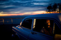CAPE TOWN, SOUTH AFRICA - JULY 24:  A man sits in his car at sunset in Cape Town, South Africa.  (Photo by Landon Nordeman) ..