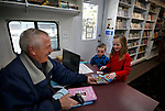 Elko County Bookmobile driver Kelvin Selders checks out books for Quincy and Natalie Dahl, 5 and 8, during a visit to the Ruby Valley School.<br />
