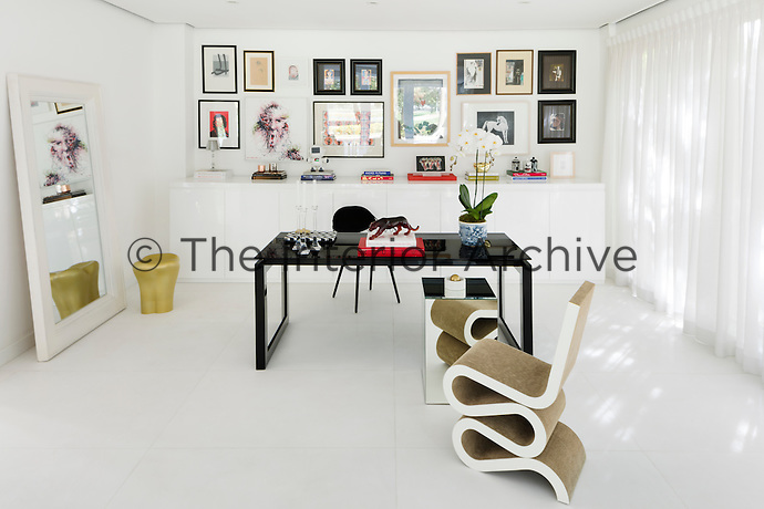 The home office is sparsely furnished with a simple desk and a Wiggle chair by Frank Gehry. A collection of artworks is displayed on the wall above a built-in cupboard unit. A Gold Tooth stool by Philippe Starck stands in front of a mirror propped up against one wall.
