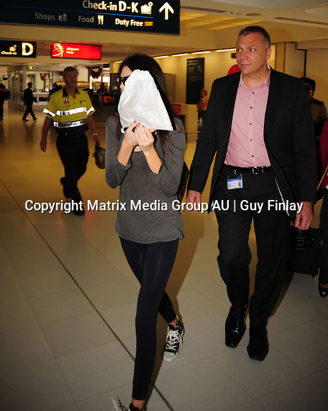 6 NOVEMBER 2012 SYDNEY AUSTRALIA<br /> <br /> EXCLUSIVE PICTURES<br /> <br /> Kendall Jenner and mother Kris Jenner leave Sydney. Pictured at Sydney International Airport departures. Kendall was not in a mood for photographers amd hid her face behind a big bag of donuts.