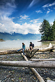 CANADA, Vancouver, British Columbia, Eric and Stepahnie Petersen sit atop drift logs at Brigade Bay on Gambier Island, in the Howe Sound with the Britannia Range in the distance