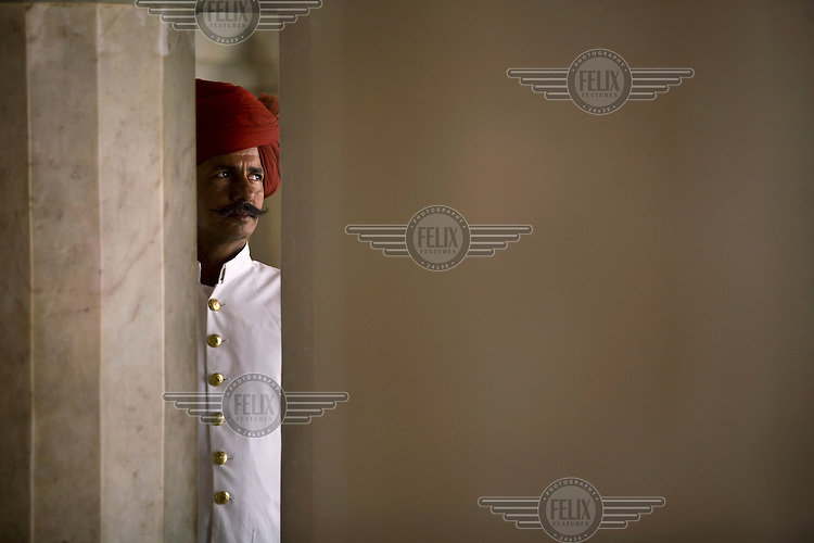 A turbaned guard looks through a column at the City Palace, Jaipur. The City Palace is a complex of palaces in central Jaipur built between 1729 and 1731 by Jai Singh II, the ruler of Amber.