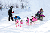 Dee Dee Jonrowe passes Tim Hewitt (UltraSport competitor) on the road just outside the village checkpoint of Ruby during the 2010 Iditarod