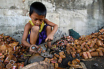 A young boy in the Philippines recycles batteries by opening them by hand, typical of the dangerous work often given to children in poor countries.