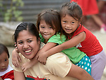 Christian Love Daroy-Gagno, the program director of the Kapatiran-Kaunlaran Foundation (KKFI), plays with children in a KKFI-sponsored preschool in Pulilan, a village in Bulacan, Philippines.<br /> <br /> KKFI is supported by United Methodist Women.