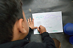 "A boy draws a picture of a house inside a ""child-friendly space"" in a refugee processing center in the Serbian village of Presevo, not far from the Macedonian border. Hundreds of thousands of refugees and migrants--including many children--have flowed through Serbia in 2015, on their way from Syria, Iraq and other countries to western Europe."