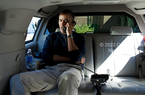 United States President Barack Obama talks on the phone with President Hamid Karzai of Afghanistan from his vehicle outside the Jane E. Lawton Community Center in Chevy Chase, Maryland, Sunday, March 11, 2012. .Mandatory Credit: Pete Souza - White House via CNP
